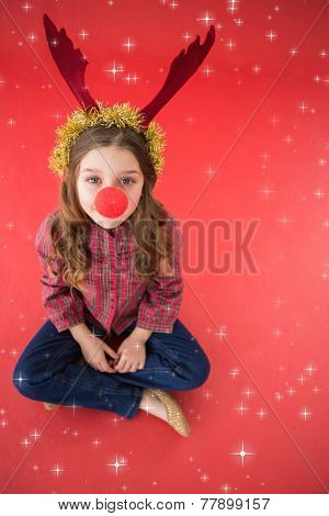 Festive little girl wearing red nose against twinkling stars