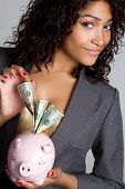 stock photo of american money  - Black woman holding piggy bank money smiling - JPG