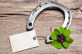 pic of horseshoe  - Horseshoe and four leaf clover with empty tag on old wooden - JPG