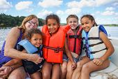 stock photo of boat  - Family in Life jackets on a boat on a lake - JPG