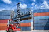 stock photo of lift truck  - Crane lifter handling container box loading to truck in import export logistic zone - JPG