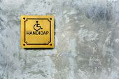 stock photo of antique wheelchair  - handicap symbol on cement background - JPG