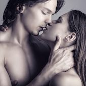 stock photo of orgasm  - Kissing young couple on a gray background - JPG