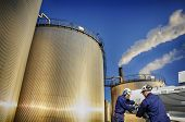 image of pipeline  - oil workers with pumps and large storage tanks - JPG