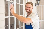 stock photo of handyman  - Handyman cleaning the window and smiling in a new house - JPG