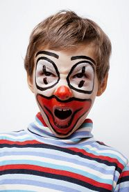 stock photo of pantomime  - little cute real boy with facepaint like clown - JPG