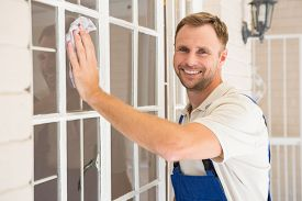 pic of handyman  - Handyman cleaning the window and smiling in a new house - JPG