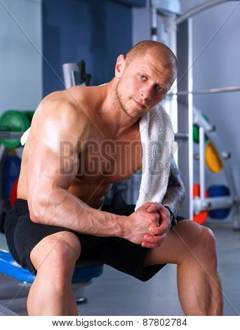 Young handsome man sits after workout in the gym