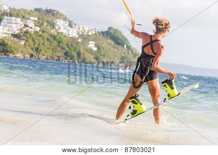 A young woman kite-surfer ready for kite surfing rides in blue sea