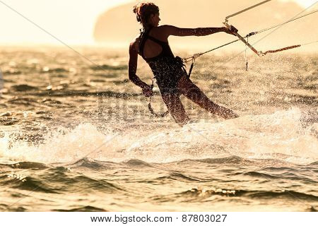 A young woman kite-surfer rides against the sun