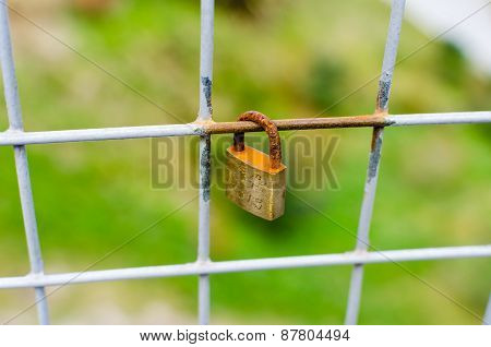 Close Up Closed Padlock Locked Onto A Square Fence With Shallow Depth Of Field - Horizontal