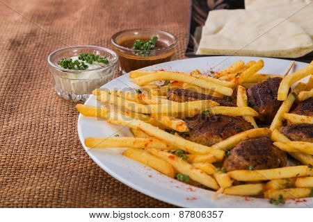 French fries with meat on a plate. Dish with delicious food.
