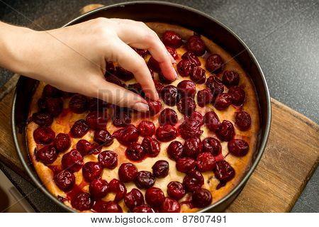 Closeup Of Female Hand Putting Cherries On Top Of Cheesecake