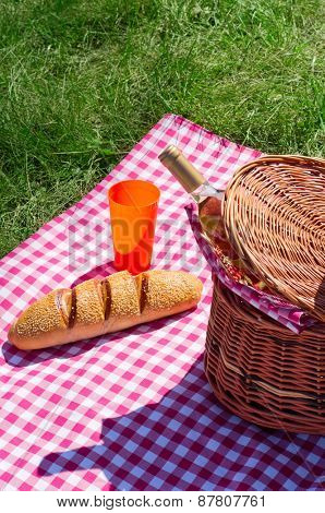 Picnic basket with wine bottle on plaid