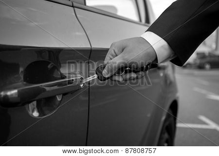 Black And White Closeup Of Man Inserting Car Key In The Hole