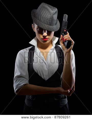 Young woman with gun on black