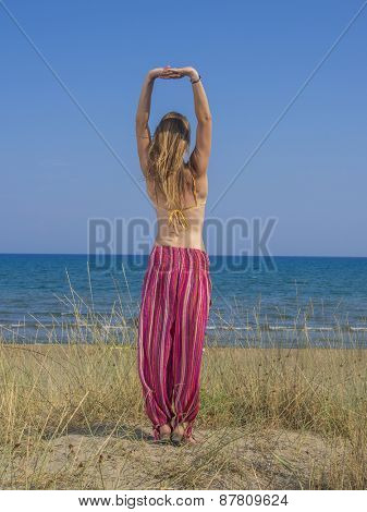 Beautiful young woman stretching during yoga on the beach