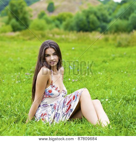 Sexy woman in long dress sitting on green grass