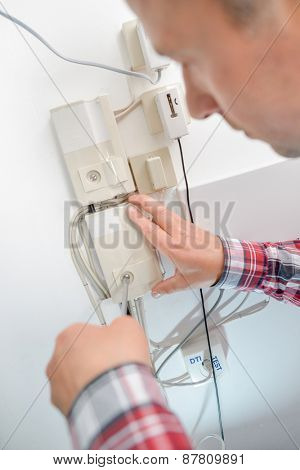 Man opening fusebox hatch with screwdriver