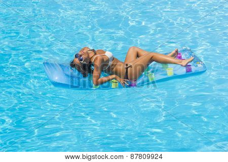 Tanned woman relaxing at the swimming pool