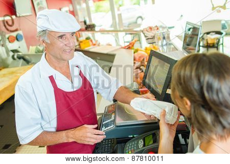 Woman buying meat from the butcher