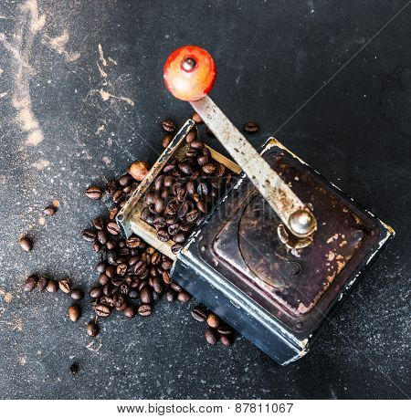 Old coffee grinder with coffee beans inside on black table