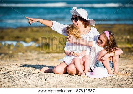 mother with two daughters on the beach