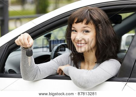 Pretty female driver in a white car showing the car key