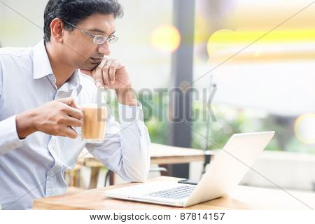 Man using laptop computer while drinking a cup hot milk tea, outdoor cafe.