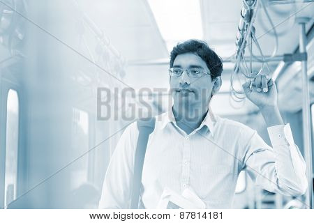 Asian Indian man taking public transport to work, standing inside bus.
