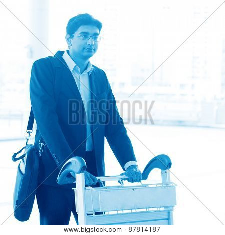 Asian Indian businessman walking with airport trolley, in blue tone.