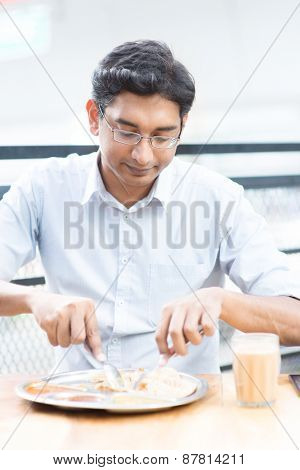 Asian Indian businessman having meal at cafeteria.