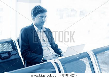 Asian Indian business man waiting his flight at airport, sitting on chair and using laptop, blue tone.