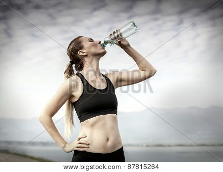 Beautiful female after running, drink water under sky