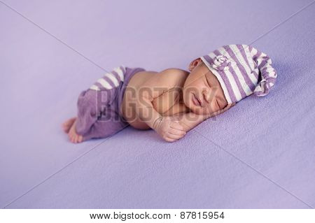 Smiling Baby Girl In A Sleeping Cap And Pants