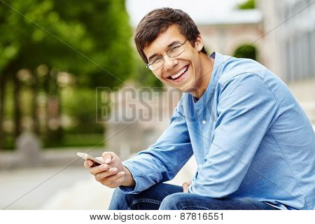 Portrait of smiling young man in glasses and blue shirt sitting in park and using mobile phone