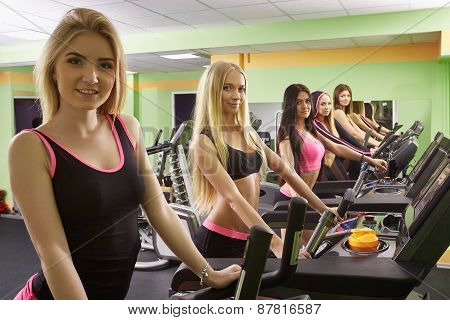 Group of lovely athletes exercising at gym
