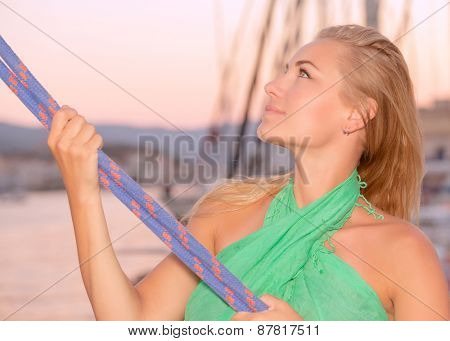 Portrait of a beautiful woman sailing, girl working on sailboat, pulling ropes, active lifestyle, enjoying traveling the world, summer vacation concept