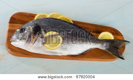 Raw Sea Bream With Lemon On  Wooden Cutting Board.