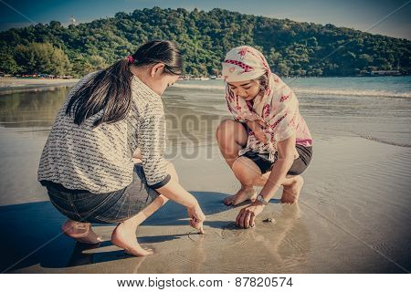 Two Asian Thai Girls Are Digging The Sand To Find Shell On The Beach Coast Of Rayong, Thailand In Vi
