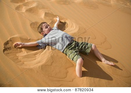 Little boy makes sand angel in desert