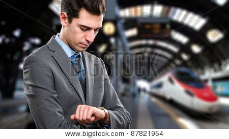 Man waiting for the train to arrive in a railroad station