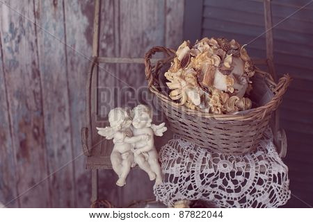 Two Plaster Angels In The Arms Sitting On A Bench On A Vintage Background Of Old Wooden Planks