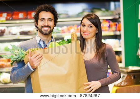 Couple holding a bag full of vegetables at supermarket