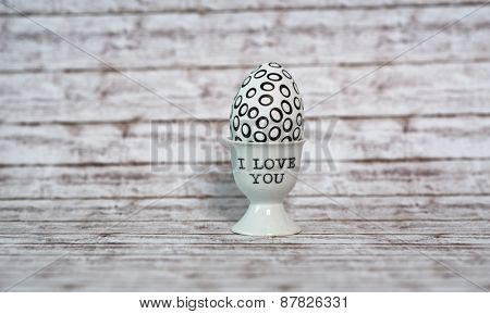 Egg with Hallow Black Circle Prints in a Porcelain White Cup with I Love You Texts on Top of the Wooden Table.