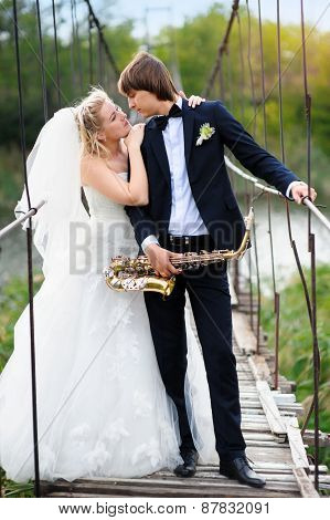 Bride And Groom On The Bridge With A Saxophone