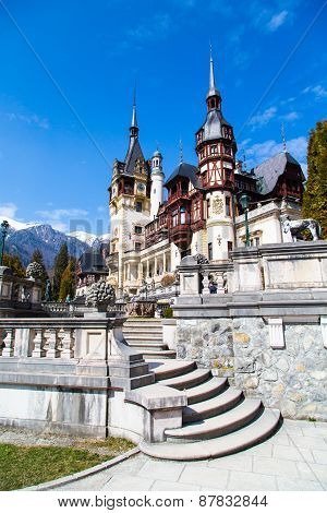 Spring view of Peles Castle with snow Bucegi Mountains in the background.