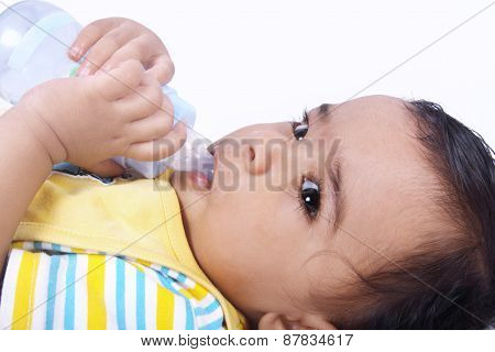 Indian baby  laying witn baby bottle