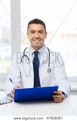 medicine, profession, technology and people concept - happy male doctor with clipboard in medical office