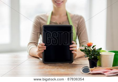 people, gardening, flowers and profession concept - close up of happy woman or gardener showing tablet pc computer black blank screen at home